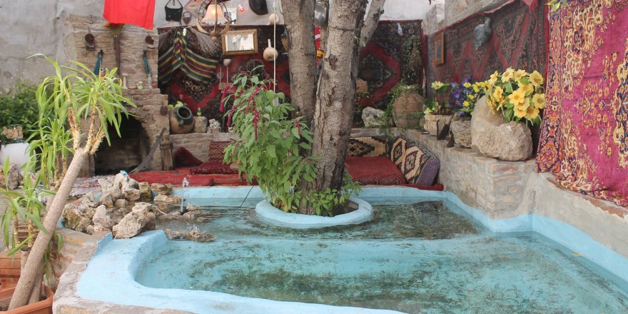 Çöpten bulduğu malzemelerle süs havuzlu şömineli bahçe yaptı